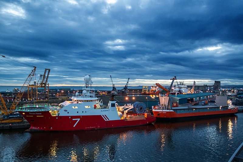 Subsea 7 vessel and red bulk vessel on harbour berth late evening at Forth Ports Leith