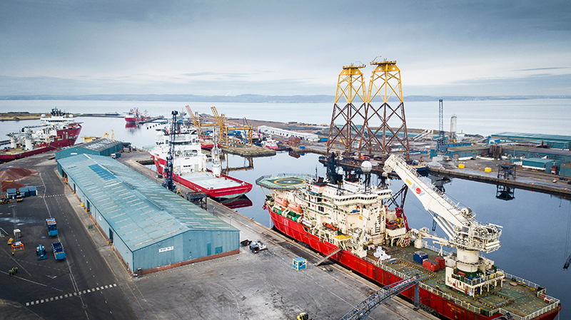 looking out over Leith harbour towards the lock entrance with 4 red NSO vessels and 2 yellow offshore wind jackets in view