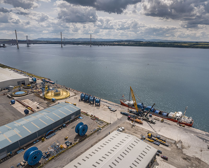 a drone view of a bulk vessel discharging and Oceaneering carousel at North Wall at Forth Ports Rosyth with Queensferry Crossing in the background