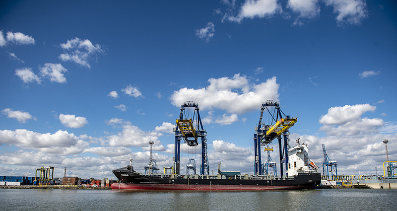 2 gantry cranes discharging container vessel at London container Terminal on sunny day