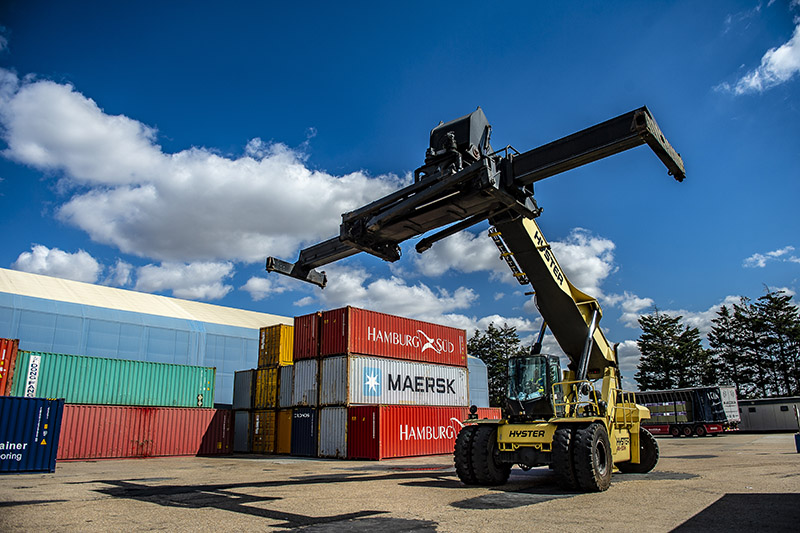 A reachstacker picking up colourful containers on a sunny day