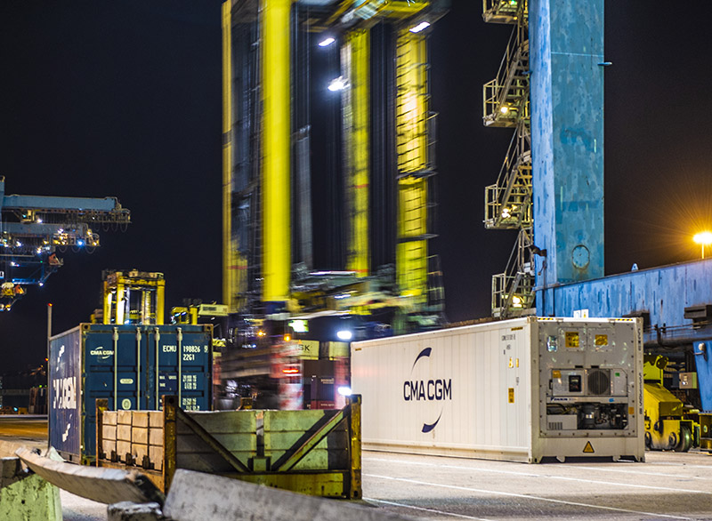 Straddle carriers moving boxes at night at London Container Terminal